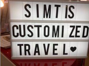 """Auf einer Leuchtbox mit schwarzen Lettern steht """"Simtis Customized Travel"""""""