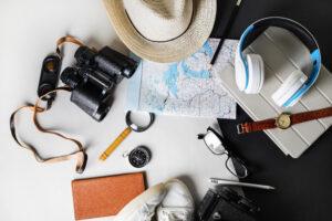 Flatlay von diversen Reise Accessoires wie einer Landkarte, Kompass, Sonnenhut und Fernglas.