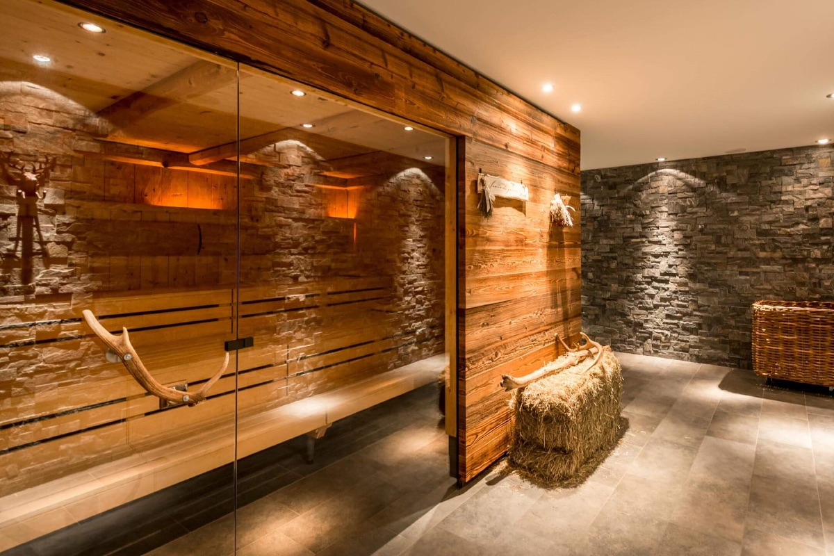 Holzsauna in einem Steinkeller. Dekoriert mit Heuballen und alten Stallelementen.
