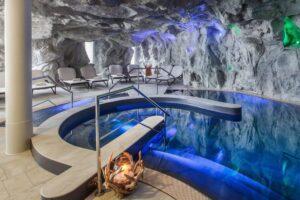 Blau beleuchteter Innenpool in einer Felsgrotte mit Liegestühlen und Kerze
