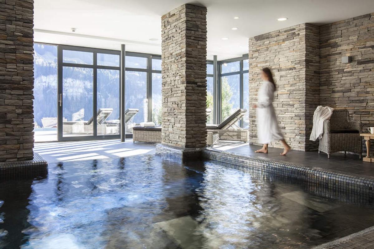 Innenpool mit Aussicht nach Draussen und eine Frau im Bademantel, die daneben steht