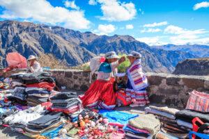 Frauen in traditionellen Trachten aus dem peruanischen Andenhochland. Verkauf von Produkten aus Alpakawolle.