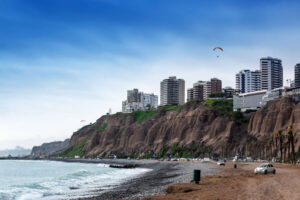 Pazifikküste vor Lima mit Meer und Strand. Im Hintergrund Skyline der Stadt und Gleitschirm.