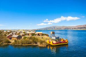 Schwimmende Schilfinseln der Uros auf dem Titicacasee zwischen Peru und Bolivien. Mit kleinen Schilfhäuschen und den typischen Booten.