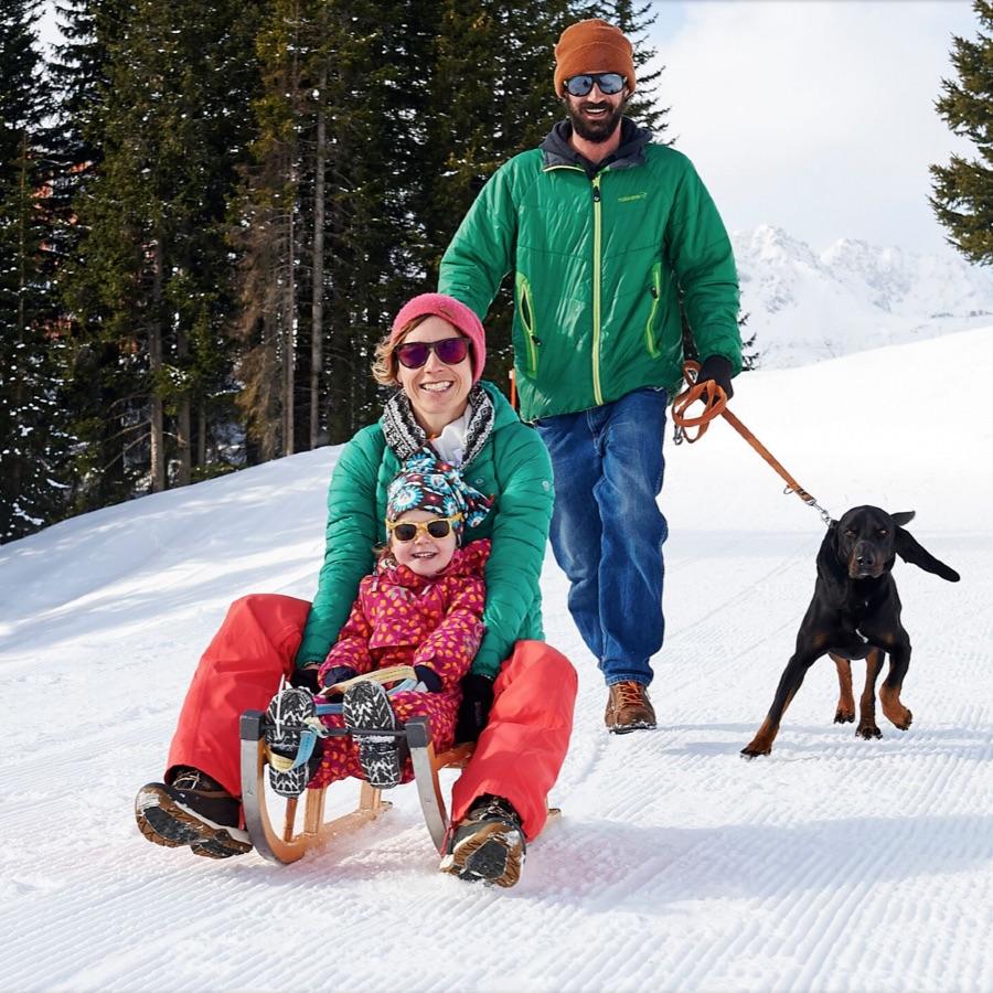 Glückliche Familie mit kleinem Kind und Hund auf Schlitten