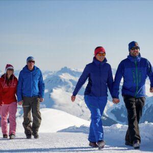 Zwei Paare bei einer Schneewanderung vor schöner Bergkulisse