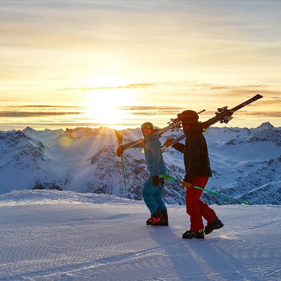 Paar mit Skiern im Schnee vor schöner Bergkulisse bei Sonnenuntergang