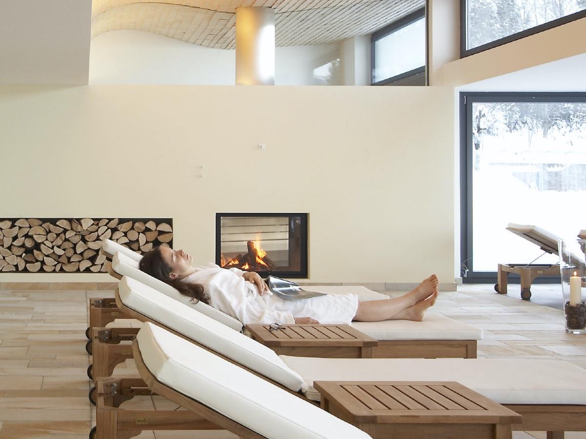 Ruheraum des Wellnessbereichs mit Liegestühlen und einem Kamin. Eine Frau liegt auf einem Liegestuhl. Vor dem Fenster liegt Schnee.