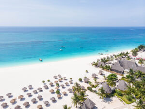 Strand vom Hotel Gold Zanzibar mit Strandschirmen, weissem Sand und türkisfarbigem Wasser