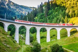 Berninaexpress auf Viadukt vor schöner Bündner Landschaft.