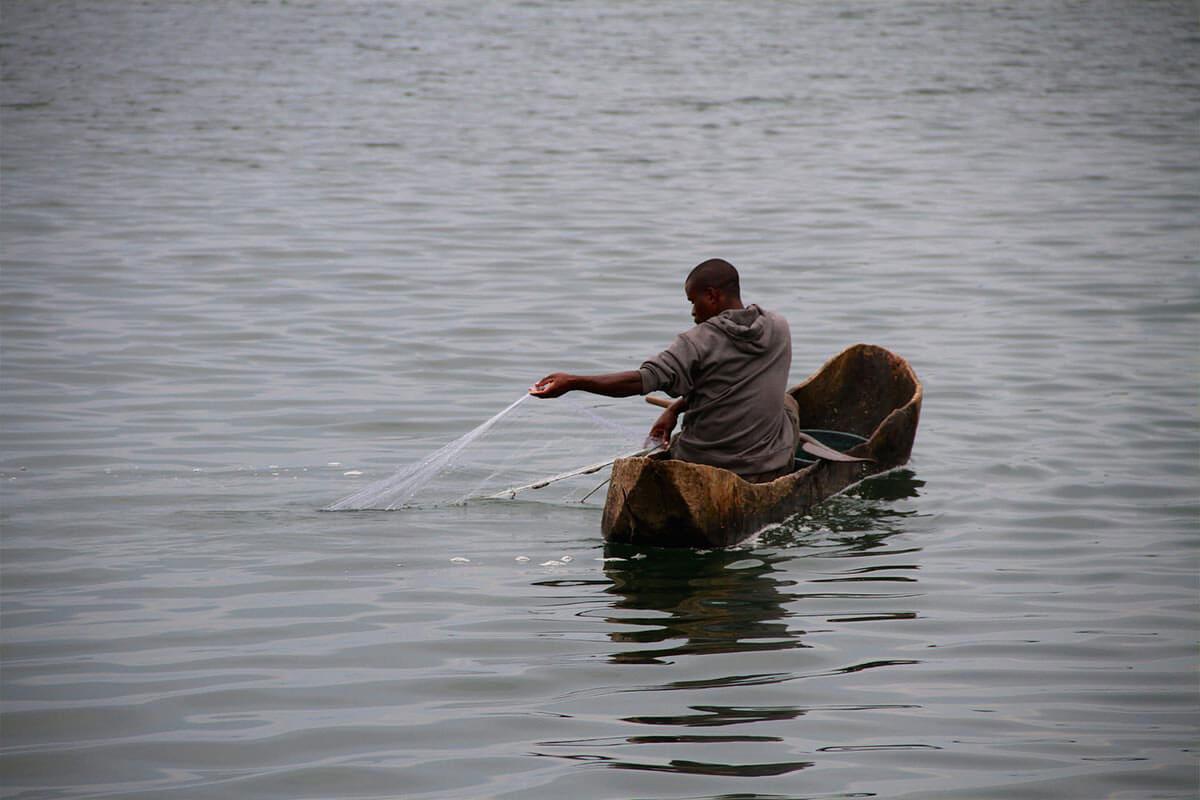 Fischer in Einbaumboot auf dem See