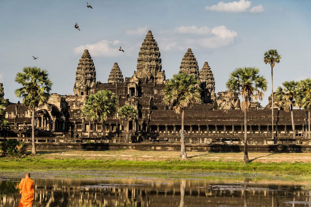 Tempelanlage Angkor Wat vor einem See mit Mönch und Palmen