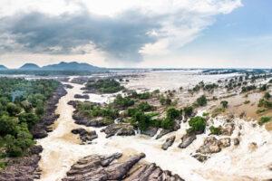 Grosser wilder Fluss mit vielen Steinen und Bäumen.