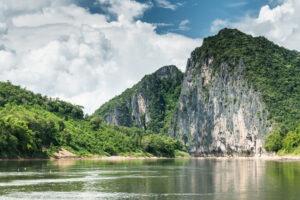 Blick vom Fluss zu zwei hohen Felsen, überwachsen mit Grün.