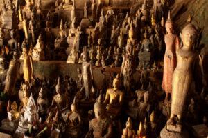 Unzählige Buddhastatuen, gross und klein, in einer Höhle.