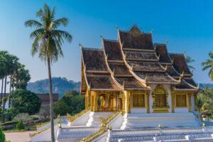 Schöner asiatischer goldener Tempel neben Palmen.