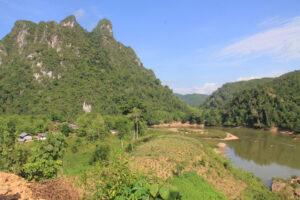 Schöne Landschaft mit hohen überwachsenen Felsen, Plantangen und einem Fluss.