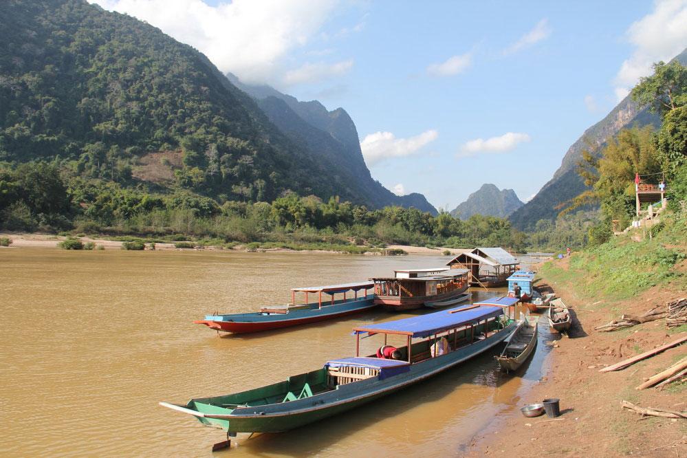 Fluss mit zwei traditionellen Holzbooten vor grüner Landschaft.