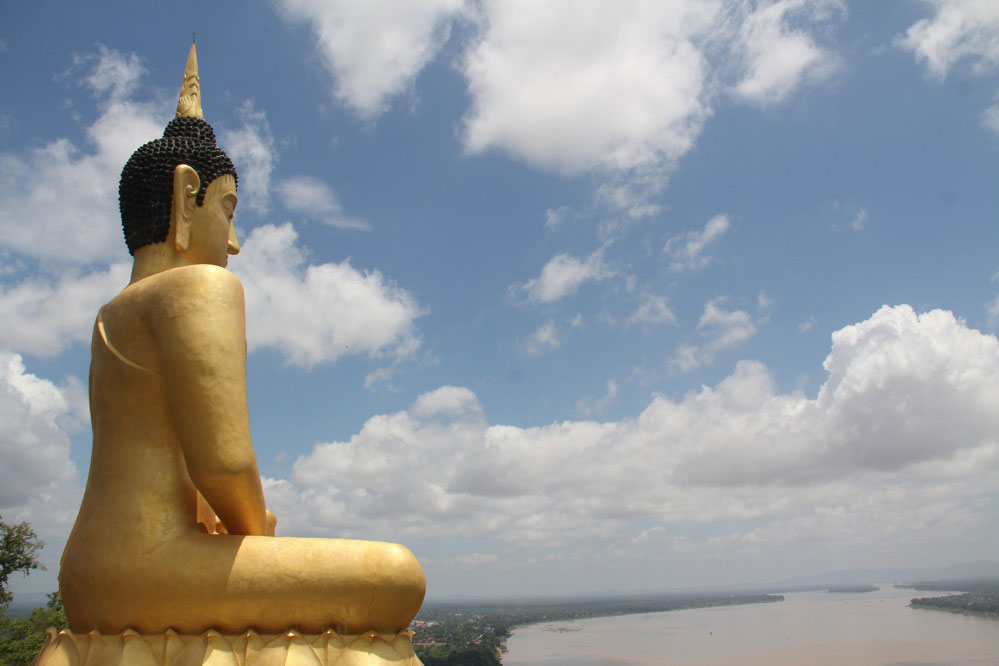 Grosser goldener sitzender Buddha mit Blick auf den Fluss
