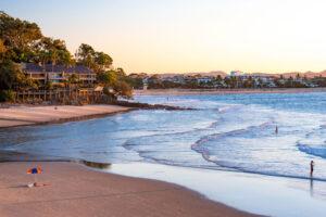 Strand von Noosa mit Blick auf die Stadt, Palmen und badenden Menschen, in schöner Abendstimmung