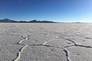 Salzwüste Salar de Uyuni mit Salzwaben vor Bergen und blauem Himmel