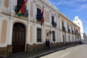 Koloniale Häuserfassade mit Bolivianischer Flagge und Kirche im Hintergrund