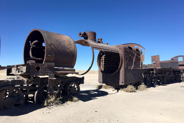 Verrostete Restteile einer Zug-Lokomotive in der Wüste