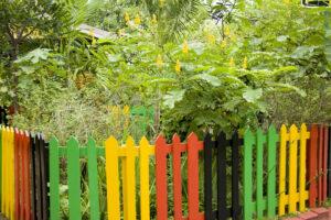 Garten mit Zaun in Jamaika-Farben (gelb, rot, schwarz, grün)