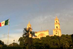 Kathedrale versteckt hinter Bäumen neben Mexikanischer Flagge
