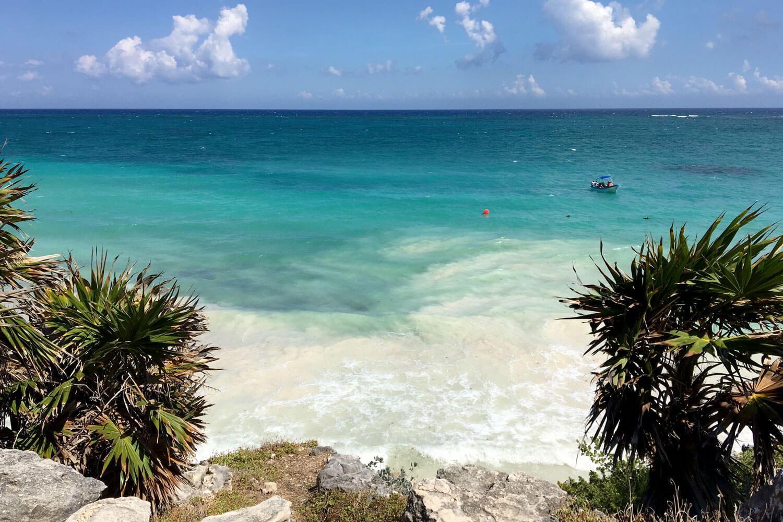 Klippe mit Blick auf karibisches Meer mit kleinem Fischerboot