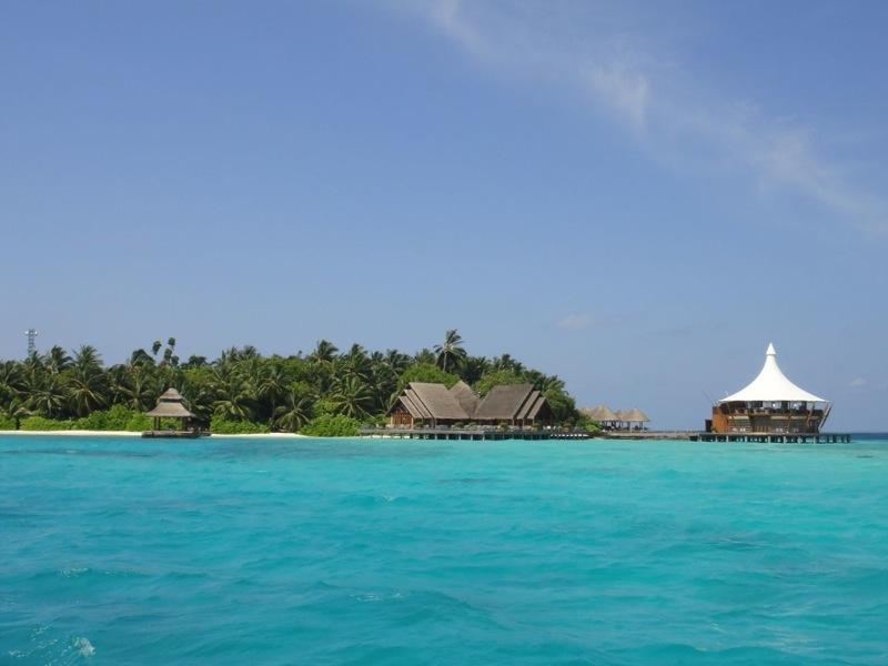 Reise in die Malediven in Asien. Bild aus Sicht vom hellblauen Meer auf das Inselresort Baros mit Bungalows auf Stelzen über dem Wasser